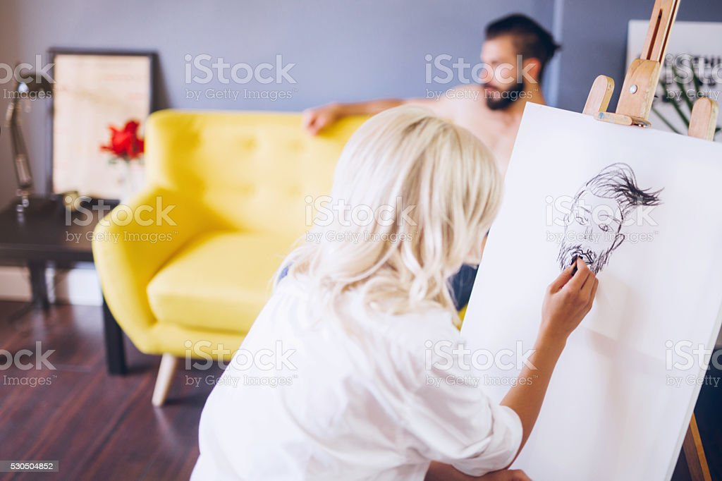 Blonde artist taking skatches of her handsome model stock photo