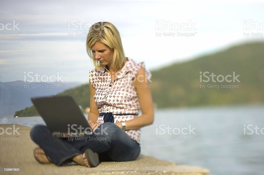 Blonde at lake using laptop stock photo