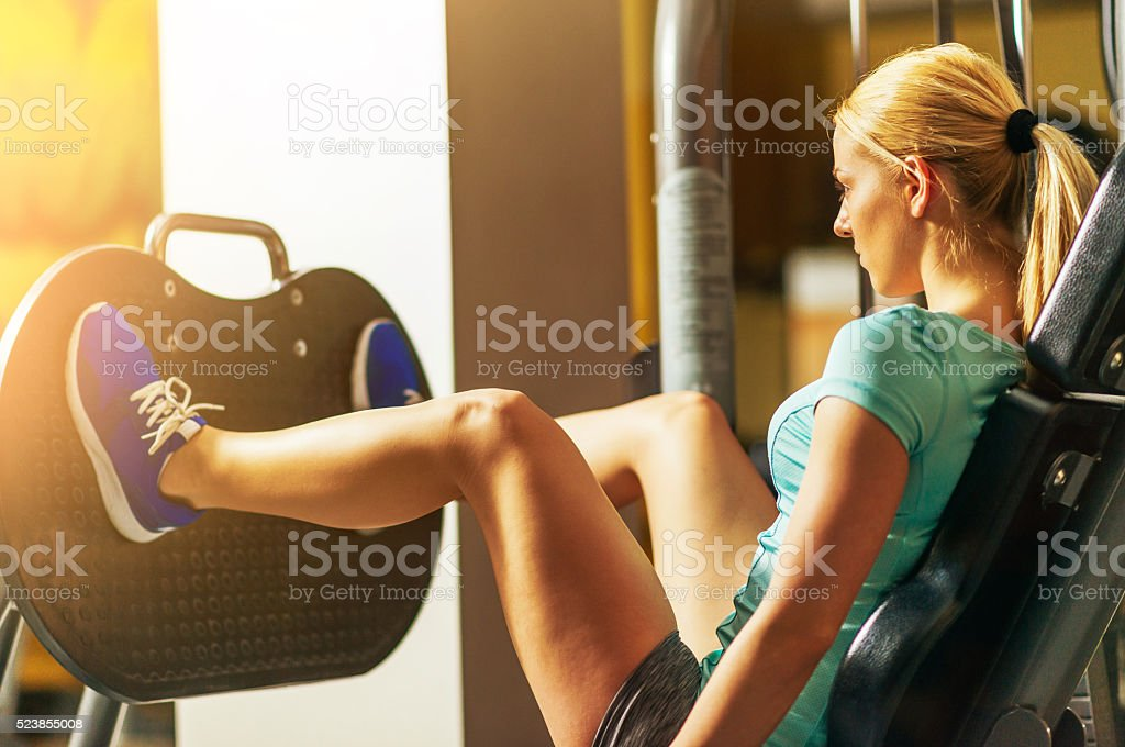 Blonde athlete doing squats in gym for buttocks and legs stock photo