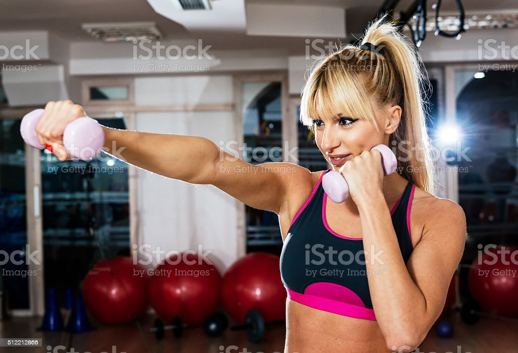 Blonde athlete exercising with weights in gym on boxing training stock photo