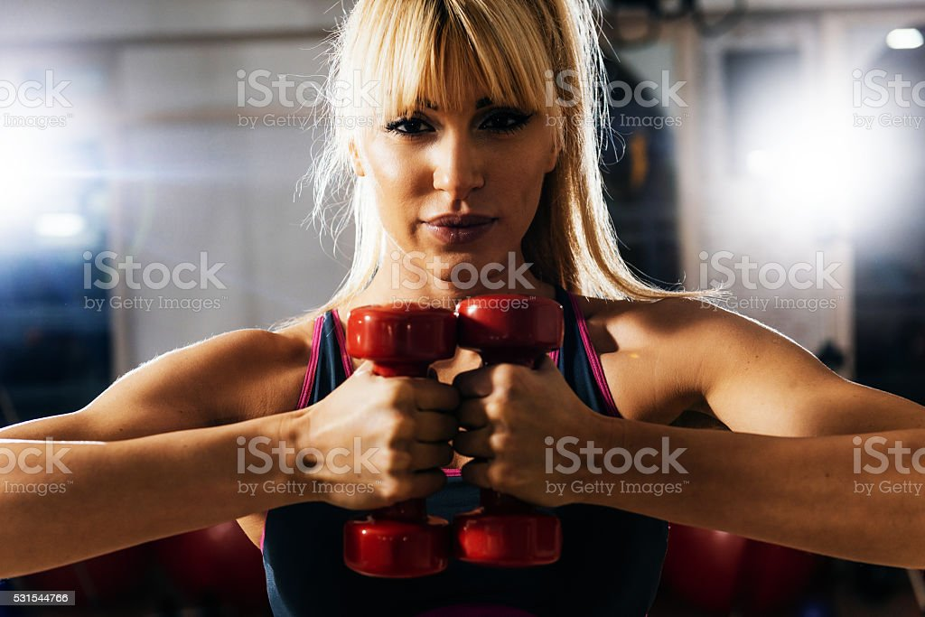 Blonde athlete exercising with weights in gym on cross training stock photo