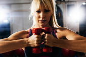Blonde athlete exercising with weights in gym on cross training