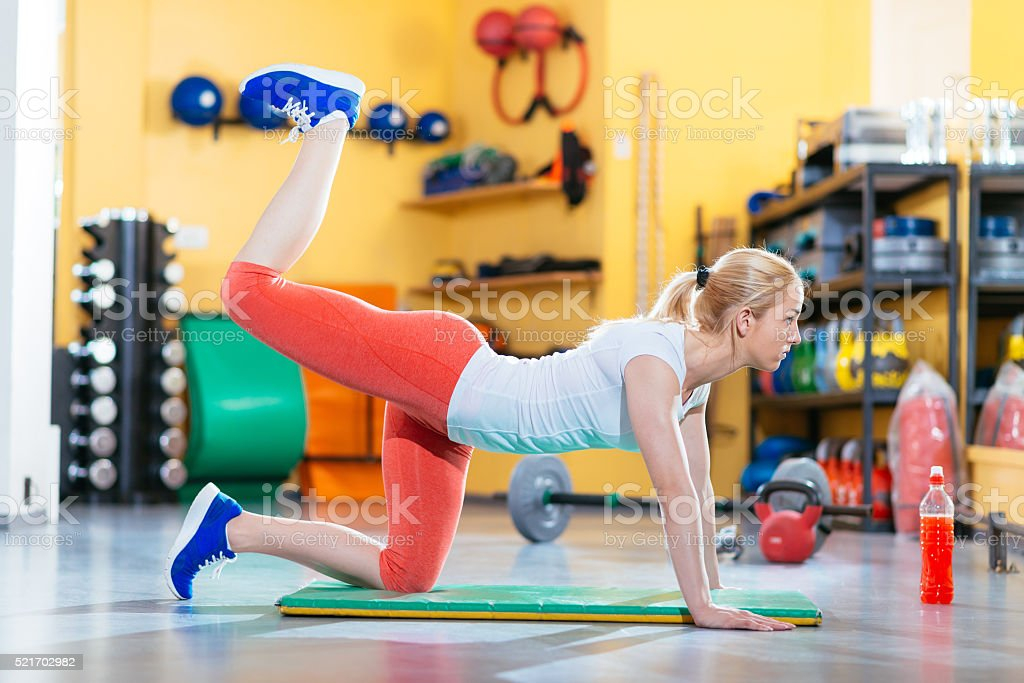 Blonde athlete lifting legs for lower back and legs stock photo