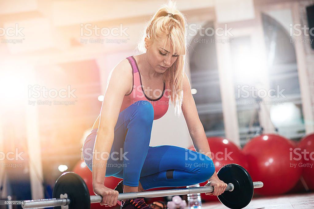 Blonde athlete lifting weights in gym for healthy lifestyle stock photo