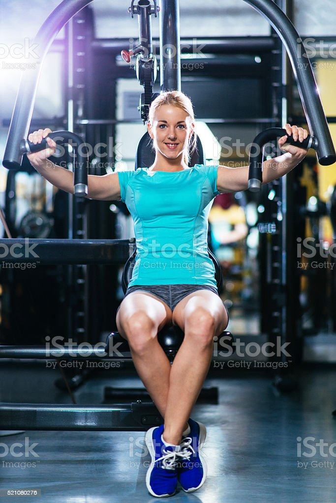 Blonde athlete pushing weights for pectoral muscles and torso stock photo