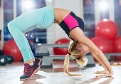 Blonde athlete stretching after training in gym and relaxes