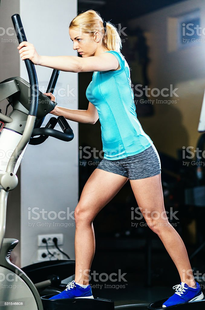 Blonde athlete uses stepper for pectoral muscles and torso stock photo