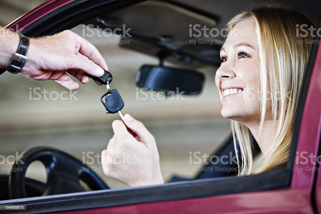 Blonde babe smiles as she receives keys to car royalty-free stock photo