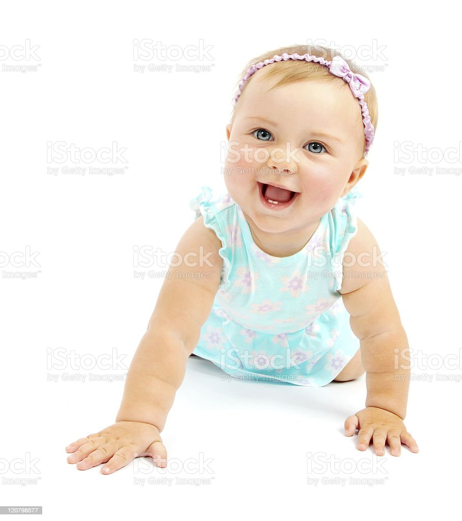 Blonde baby girl in blue dress holding herself up & smiling stock photo