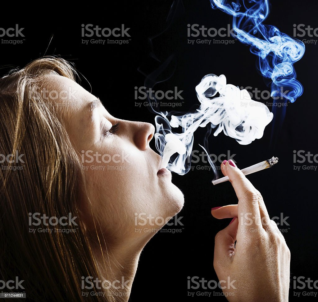 Blonde beauty dreamily smoking a marijuana joint stock photo