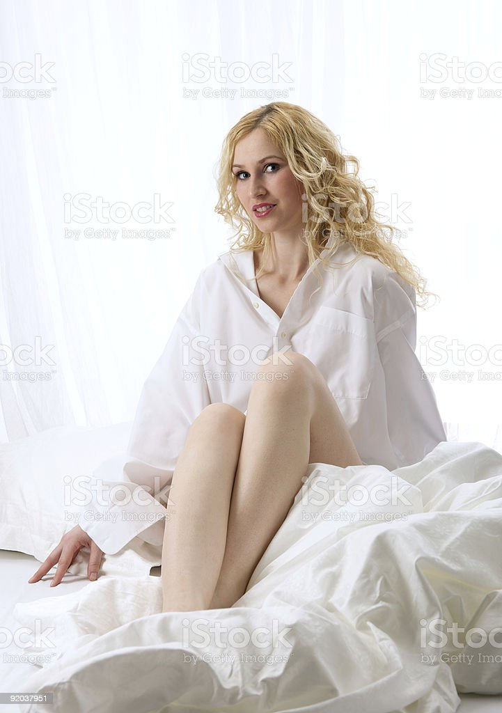 Blonde beauty sitting on her white bed royalty-free stock photo
