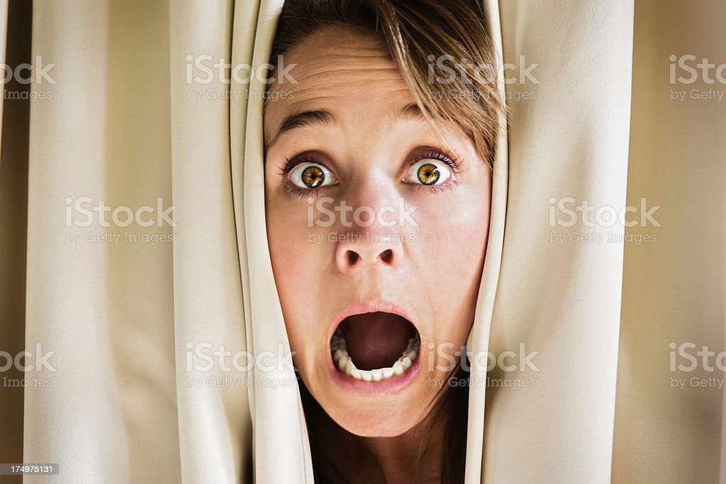 Blonde behind curtains screams in terror royalty-free stock photo