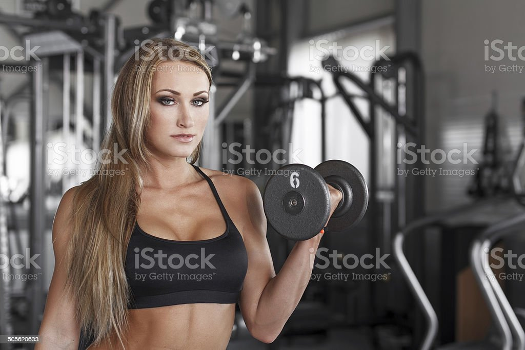Blonde bodybuilder workout with dumbbell royalty-free stock photo