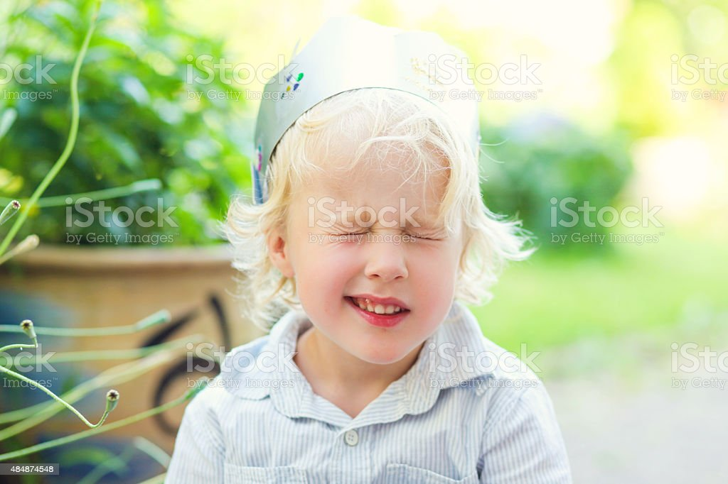 Blonde boy blinks his eyes stock photo
