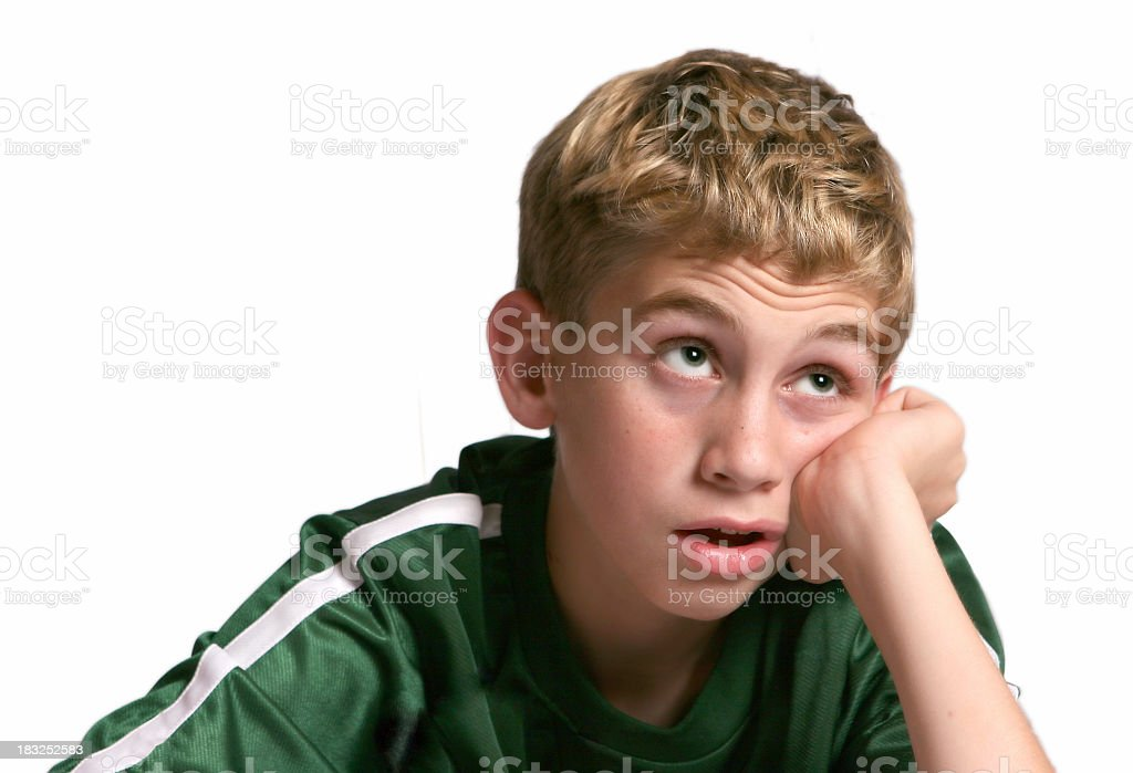 Blonde boy in green shirt staring up with bored expression stock photo
