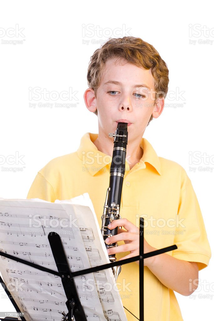 Blonde boy in yellow shirt practicing clarinet royalty-free stock photo