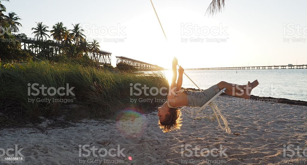 Blonde Boy on Rope Swing at Beach on Sunset stock photo