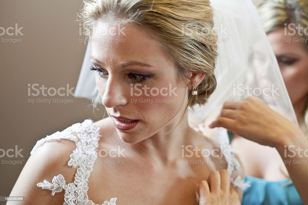 Blonde bride having her dress and veil prepared for wedding stock photo