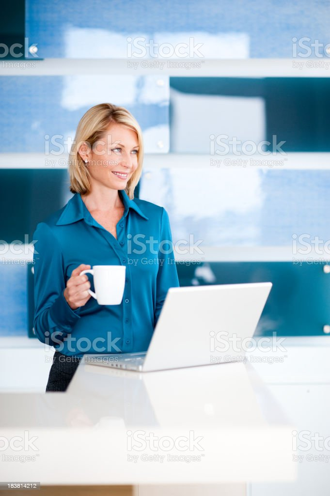 Blonde Business Woman Drinking Coffee with Laptop Computer royalty-free stock photo