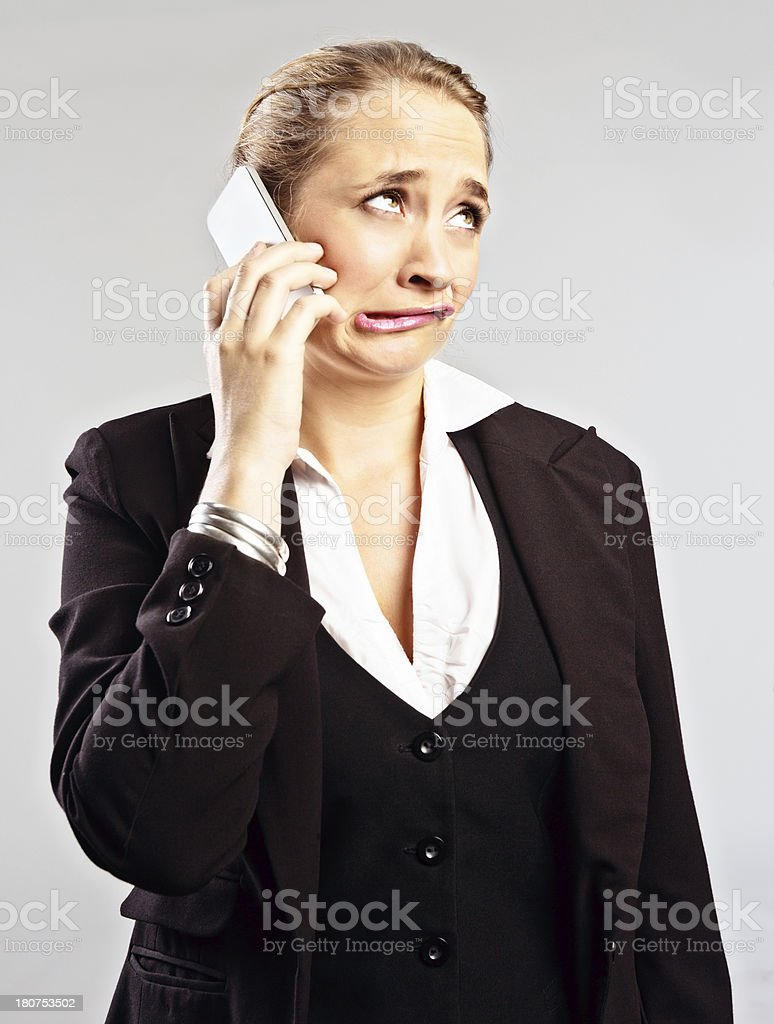 Blonde businesswoman grimaces as she listens to cellphone stock photo