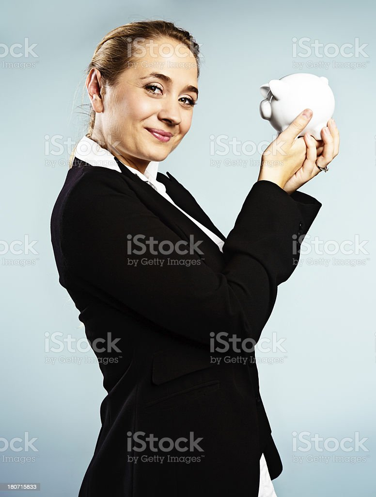 Blonde businesswoman holding piggybank is happy with her savings stock photo