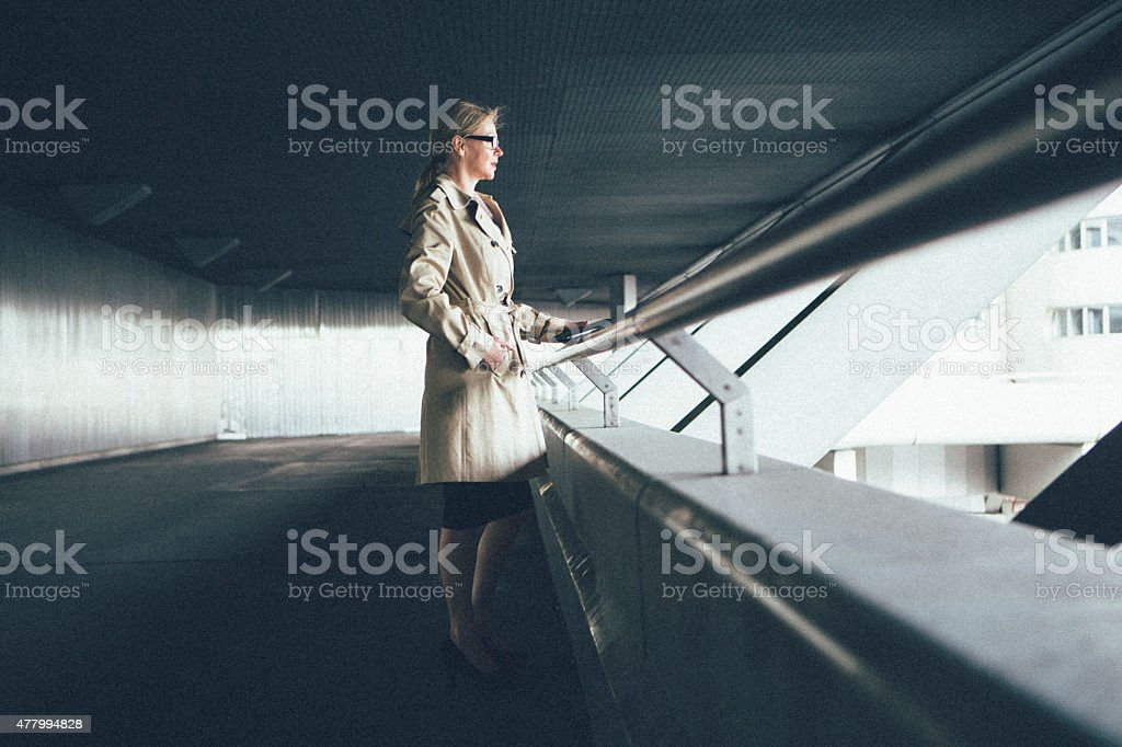 blonde businesswoman leans at railing looking away stock photo