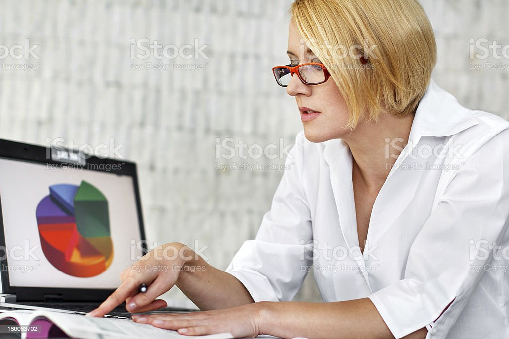 Blonde businesswoman reading laws royalty-free stock photo