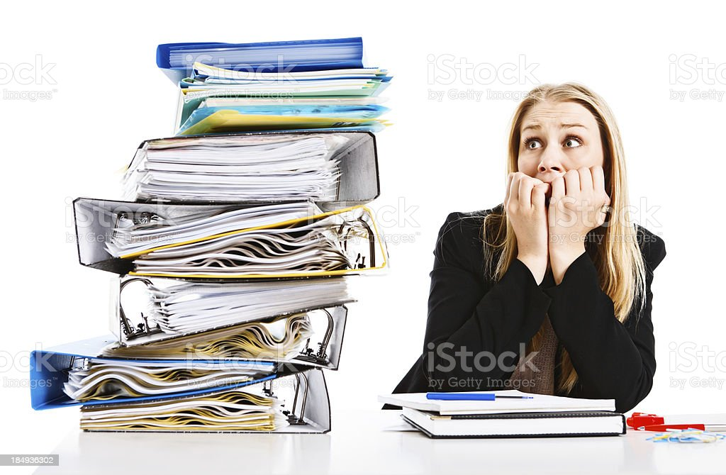 Blonde businesswoman recoils from huge pile of work royalty-free stock photo