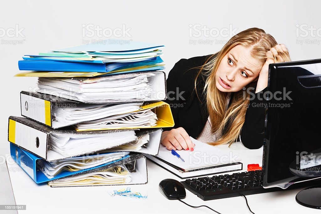 Blonde businesswoman tears hair out in frustration at workload royalty-free stock photo