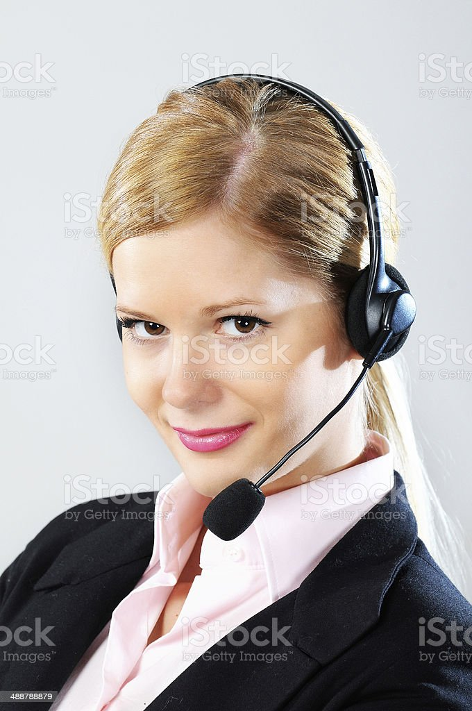 Blonde businesswoman with headphones in formal outfit in call center stock photo
