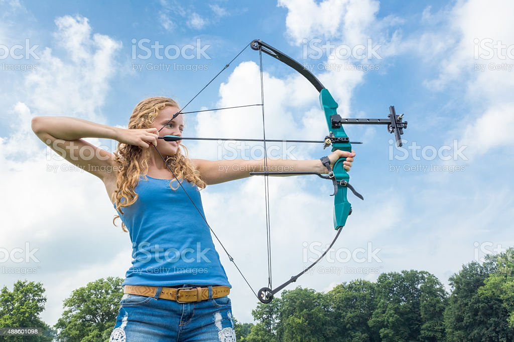 Blonde caucasian girl shooting with arrow and compound bow stock photo