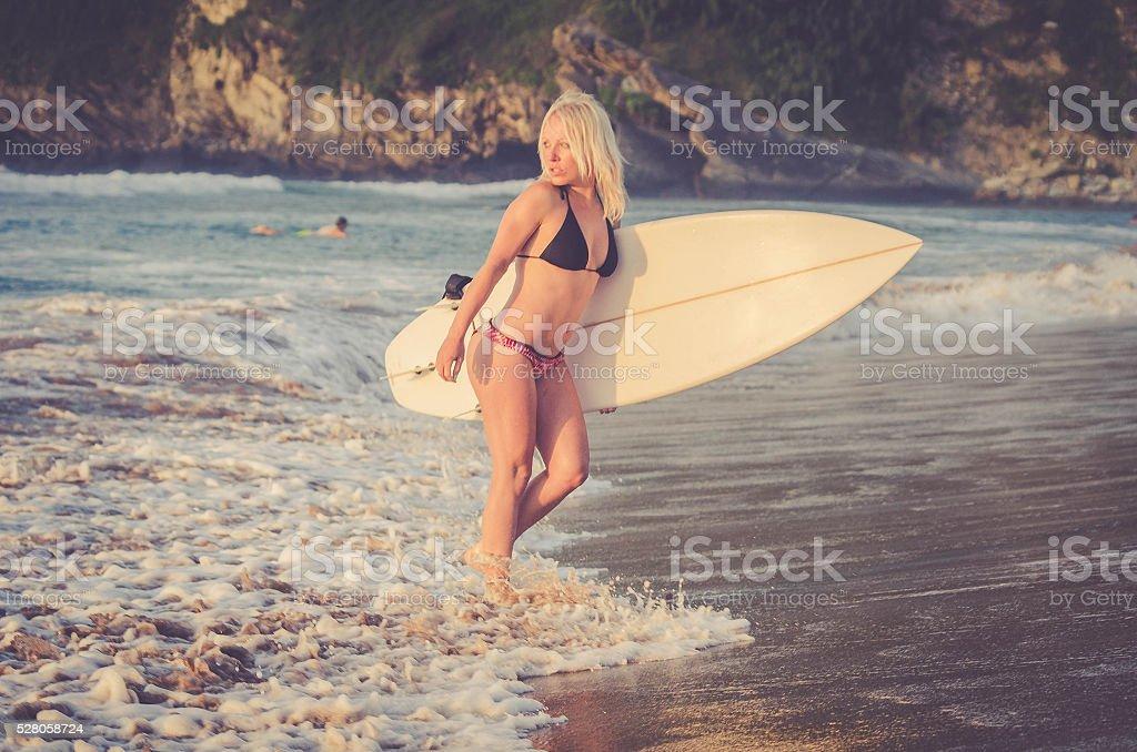 Blonde Caucasian Surfer Girl - Sunset on Atlantic Surf Beach stock photo