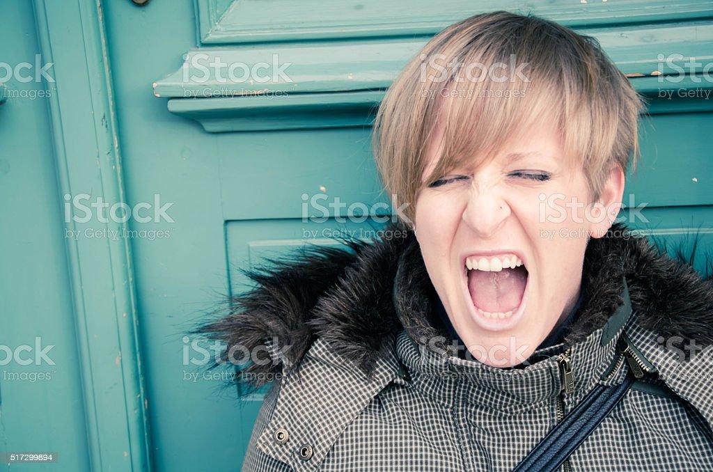 Blonde caucasian woman in front of green door, Gorizia Italy stock photo