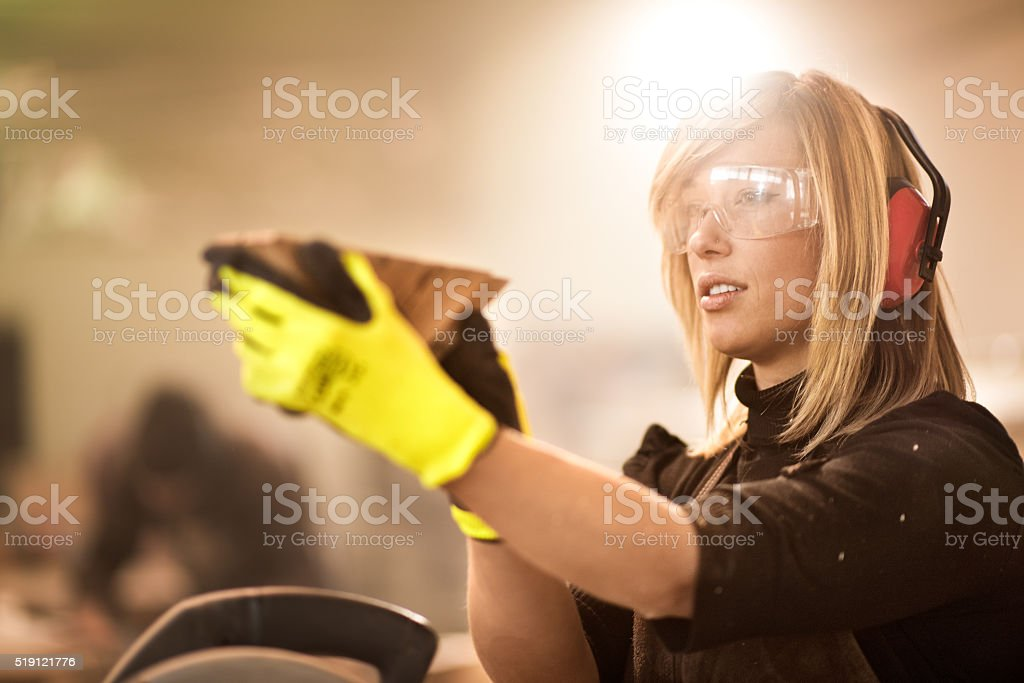 Blonde craftsperson looking at furniture part stock photo
