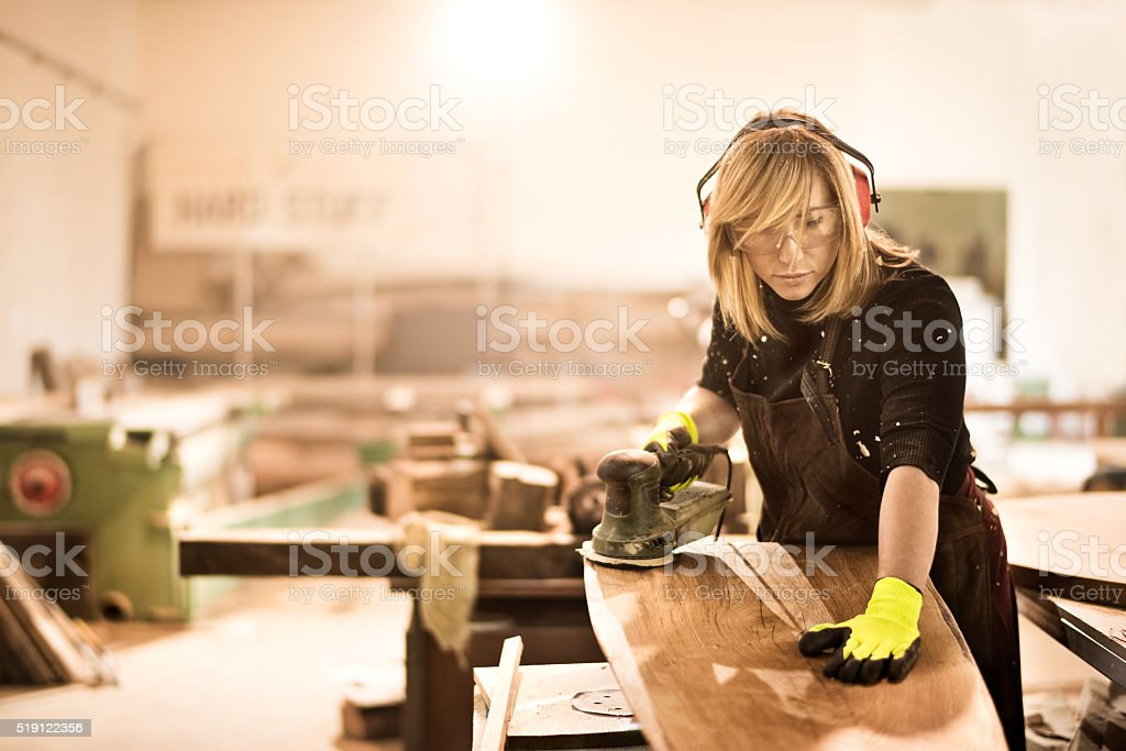 Blonde craftsperson power sanding wood stock photo