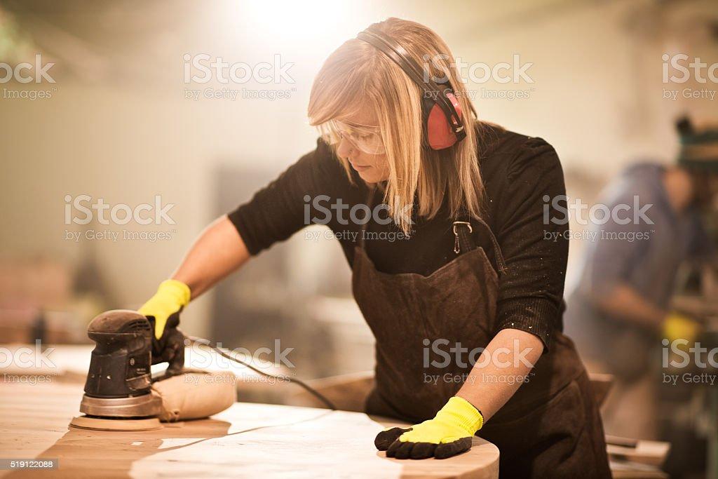 Blonde craftsperson working with power sander stock photo