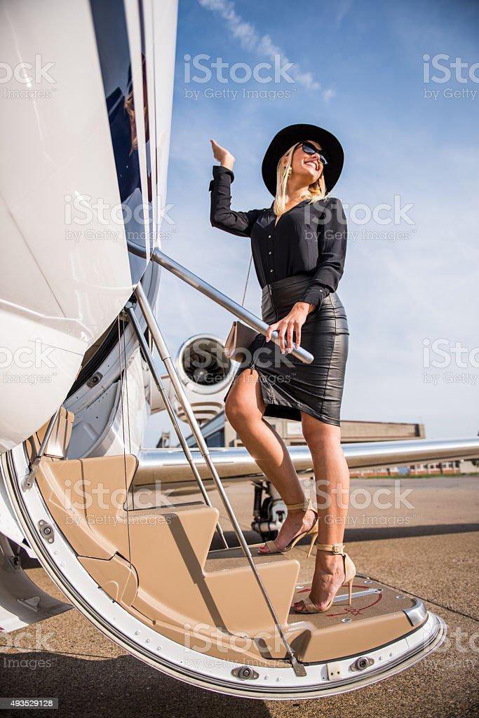 Blonde elegant woman entering private aeroplane stock photo