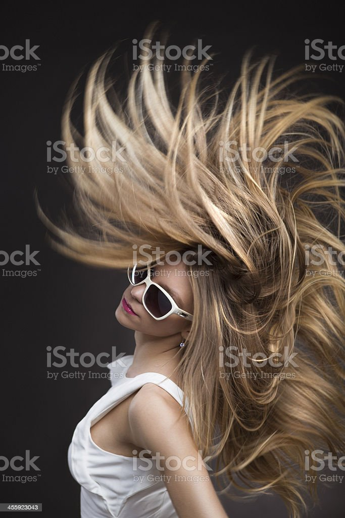 Blonde fashion model in white sunglasses whipping her hair stock photo