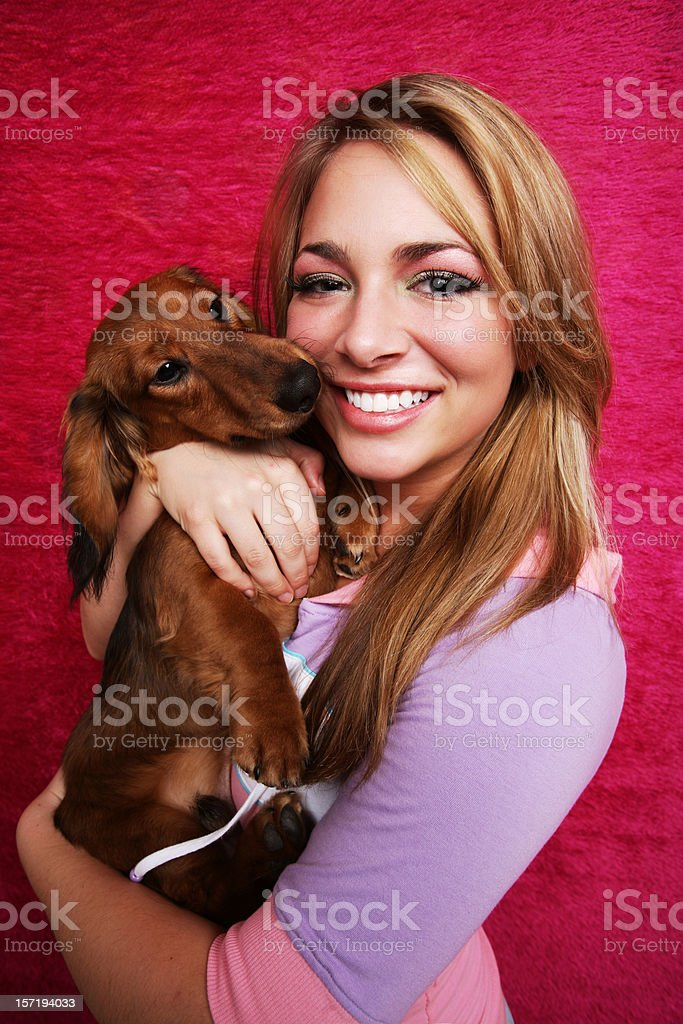 Blonde Female Holding Puppy Against Pink Background stock photo