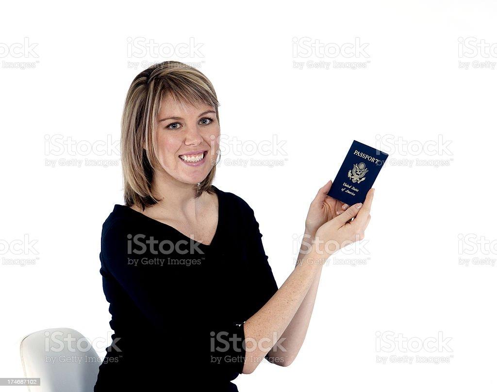 Blonde female looking into camera holding passport stock photo