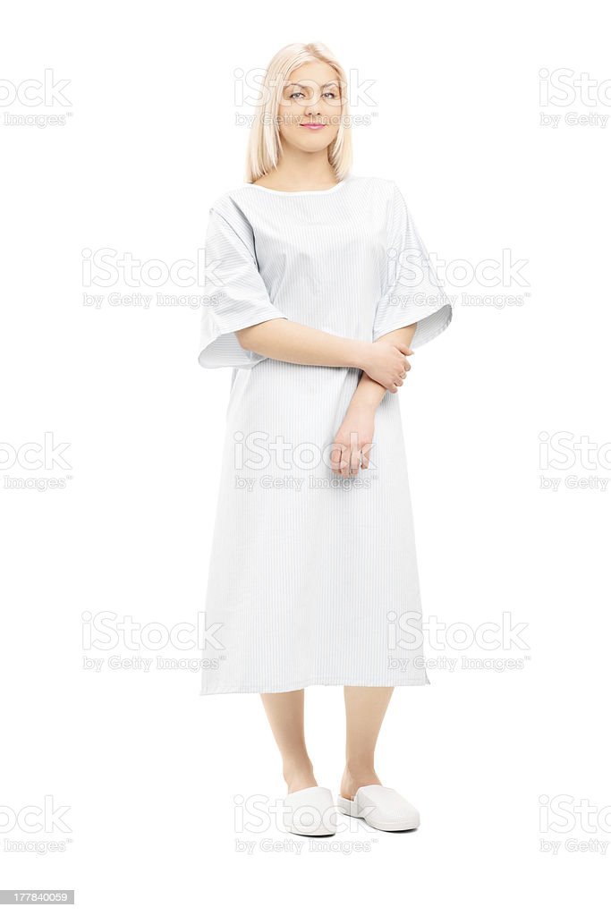 Blonde female patient wearing a white hospital gown stock photo