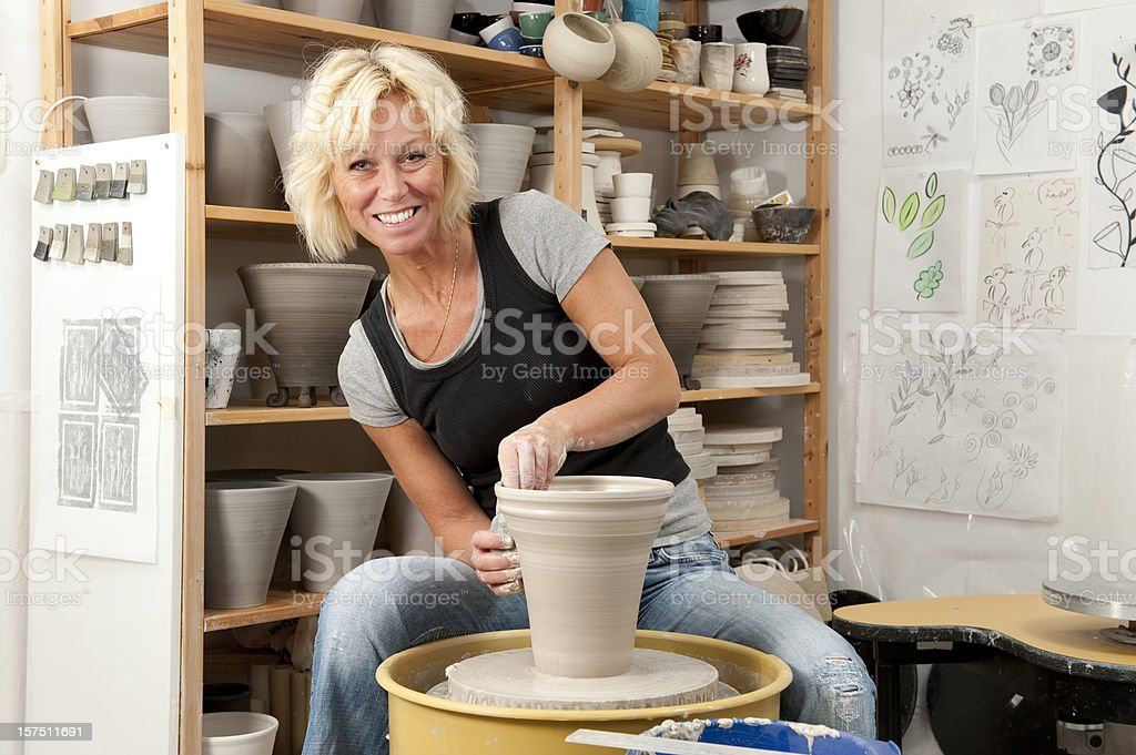 Blonde female potter sits at the pottery wheel stock photo