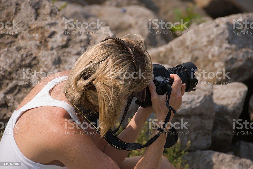 Blonde female SLR photographer royalty-free stock photo