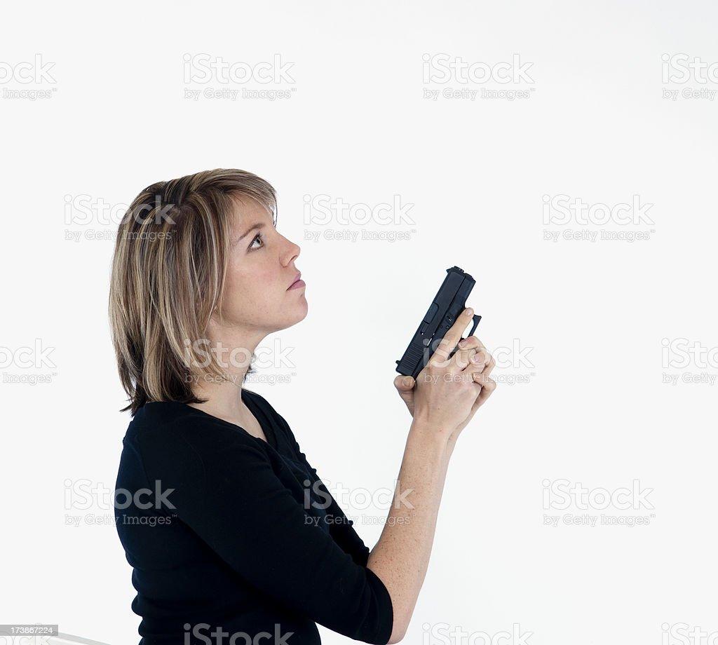 Blonde female with handgun looking up stock photo