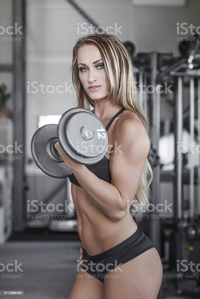 Blonde fitness model workout with dumbbell royalty-free stock photo