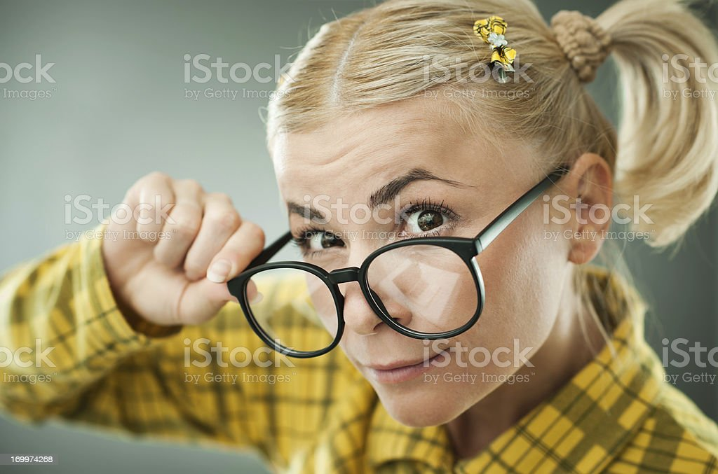 Blonde geek holding her glasses. royalty-free stock photo