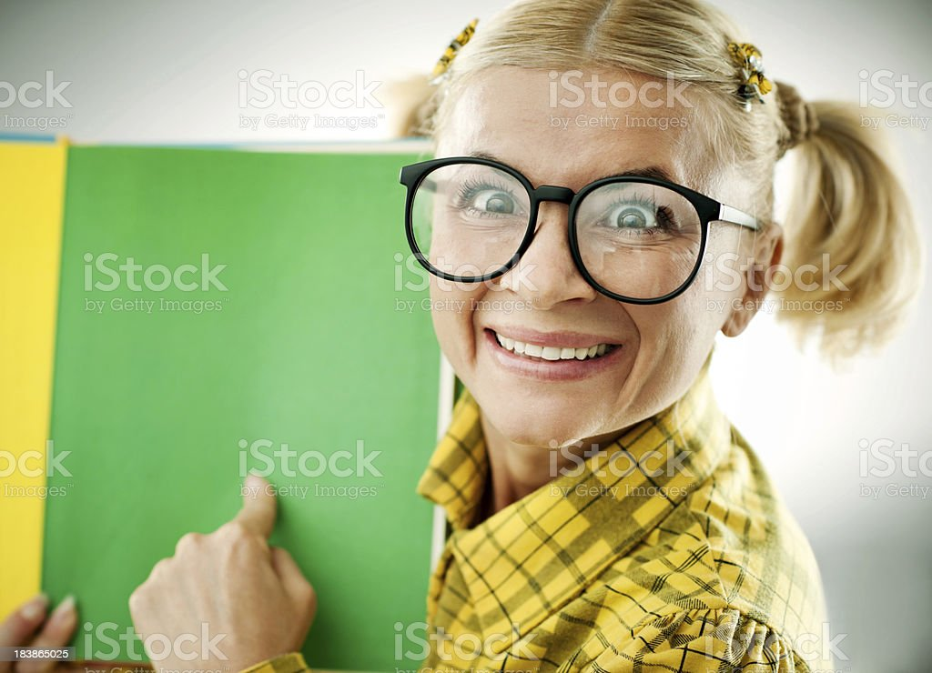 Blonde geek pointing to a green book. royalty-free stock photo