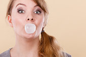 Blonde girl chewing gum making balloon.
