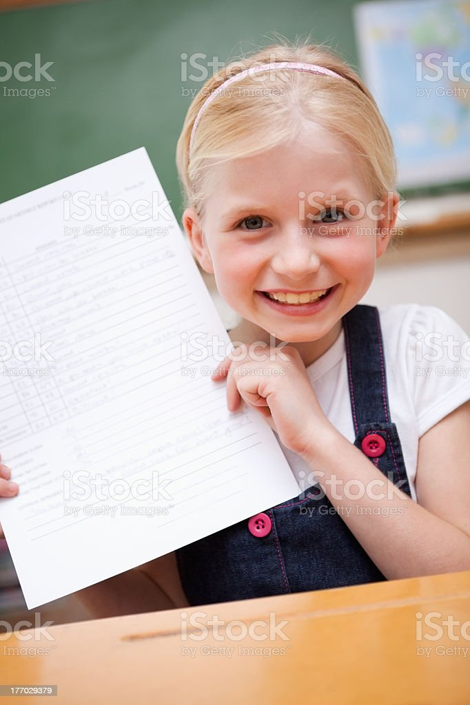 Blonde girl dressed in blue and white holds up school report stock photo