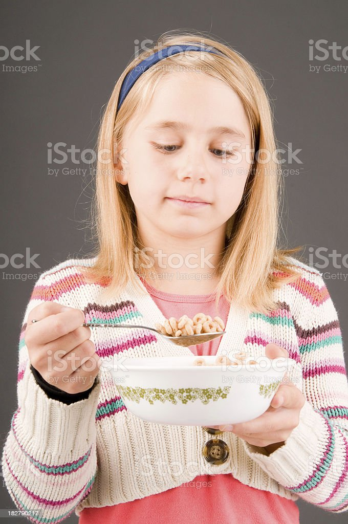 Blonde girl eating cereal stock photo